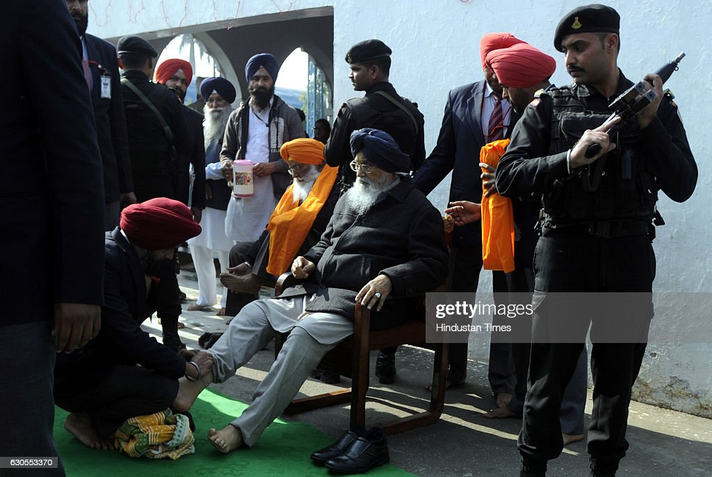 A security person helping Punjab Chief Minister Parkash Singh Badal in wearing his shoes while coming out of the historic Gurudwara Fategarh Sahib on.