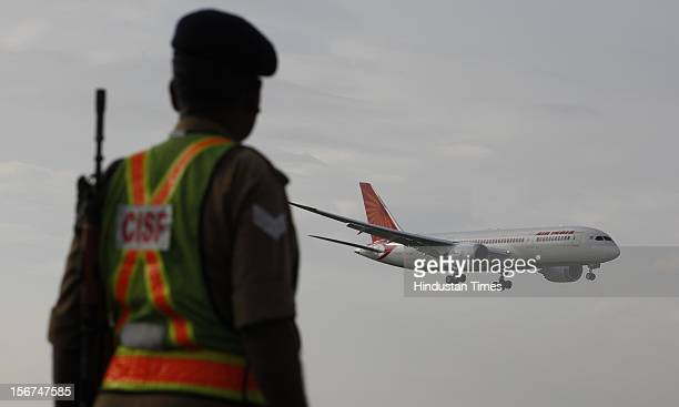 'NEW DELHI INDIA SEPTEMBER 8 Security person watch as the new member of Air India advanced Boeing 787 Dreamliner touched down at IGI airport on...