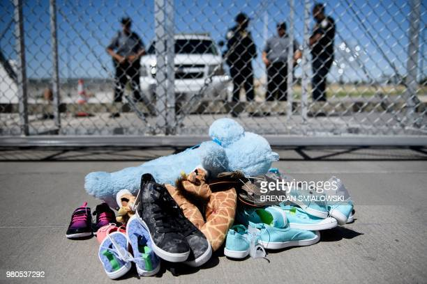 TOPSHOT Security personal stand before shoes and toys left at the Tornillo Port of Entry where minors crossing the border without proper papers have...