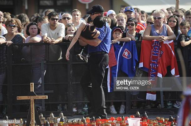 Security personel carries a fainted woman from the crowd of a farewell ceremony at the Old Town Square on September 11 2011 in Prague to pay tribute...