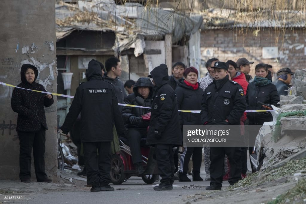 Security personel (front) cordon off the site of a fire in a low income neighbourhood in Beijing on December 13, 2017. A building fire killed five people and injured eight in one of Beijing's migrant neighbourhoods, just weeks after local authorities began mass evictions in response to another deadly blaze. /