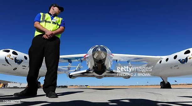 Security personel mans his position in front of WhiteKnightTwo, carrying SpaceShipTwo, outside the Spaceport America Terminal Hangar Facility at...