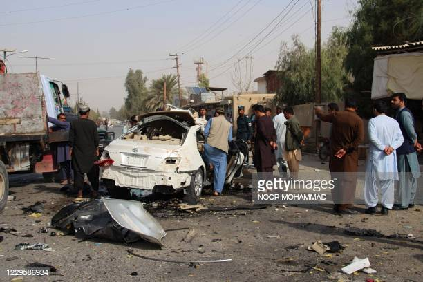 Security personnel and onlookers stand at the site of a blast along the roadside in Lashkar Gah, the capital of Helmand province on November 12,...