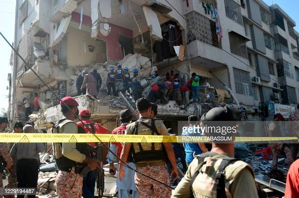 Security personnel and rescue workers are seen amid the debris of a multi-storey building that was damaged after an explosion in Pakistan's port city...