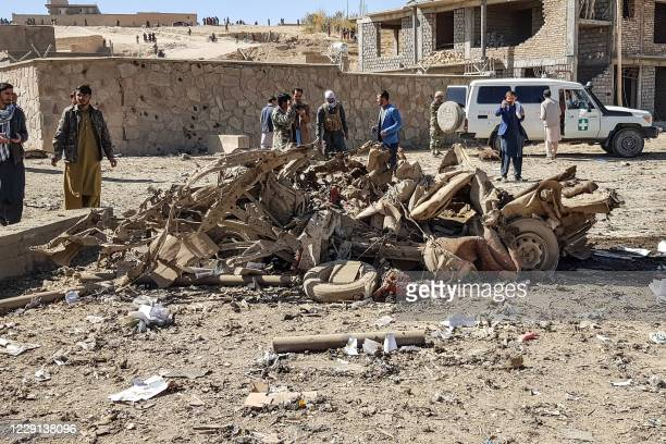 Security personnel and residents gather around the site of a car bomb attack that targeted an Afghan police headquarters in Feroz Koh, the capital of...