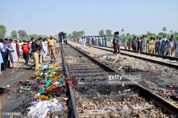 Security personnel and residents gather on a rail track after a passenger train caught on fire near Rahim Yar Khan in Punjab province on October 31...