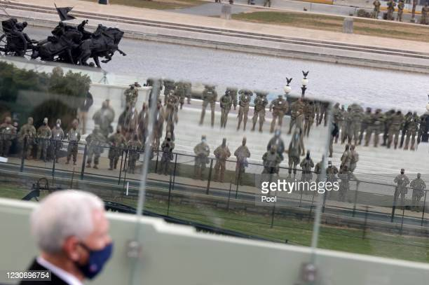 Security personnel are reflected in glass as U.S. Vice President attends the inauguration of U.S. President-elect Joe Biden on the West Front of the...