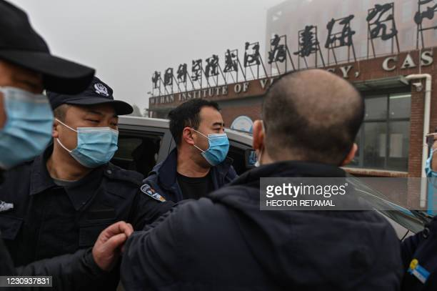 Security personnel are seen as members of the World Health Organization team investigating the origins of the COVID-19 coronavirus, arrive at the...