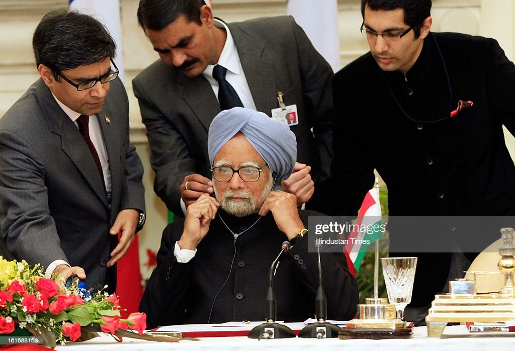 Security personnel assists Indian Prime Minister Manmohan Singh to wear an ear phone as he sits with French President Francois Hollande, unseen, during signing of agreements on February 14, 2013 in New Delhi, India.