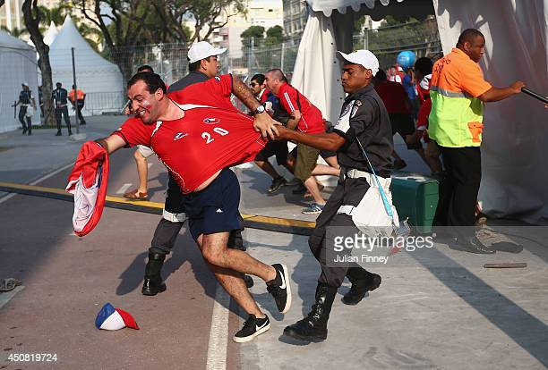 Security personnel attempt to control Chilean fans outside the stadium prior to the kickoff of the 2014 FIFA World Cup Brazil Group B match between...