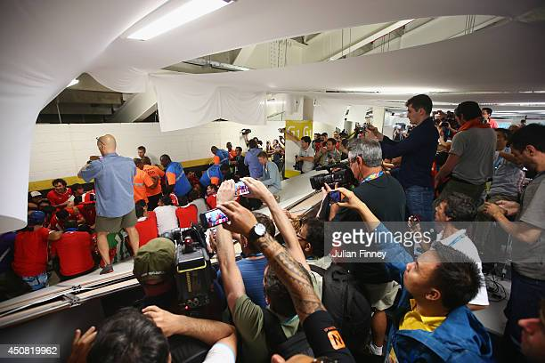Security personnel attempt to control fans after breaking through security and entering the stadium prior to the 2014 FIFA World Cup Brazil Group B...