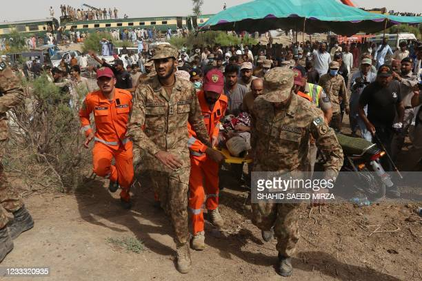 Security personnel carry an injured passenger to an army helicopter at the site of a train accident in Daharki area of the northern Sindh province on...