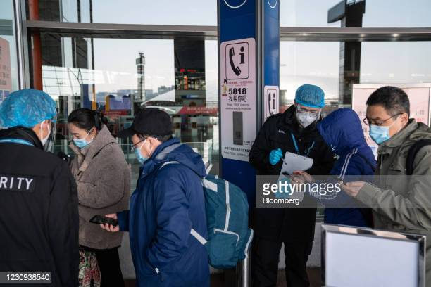 Security personnel check the health codes of travelers on smartphones at an entrance to Beijing Capital International Airport ahead of Lunar New Year...