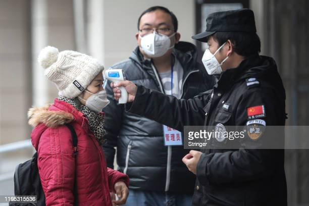 Security personnel check the temperature of passengers in the Wharf at the Yangtze River on January 22, 2020 in Wuhan, Hubei province, China. A new...