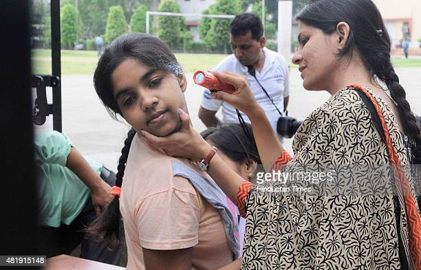 Security personnel checks an AIPMT aspirant's ear for any bluetooth device at the entrance of an examination center at a school during All India Pre...
