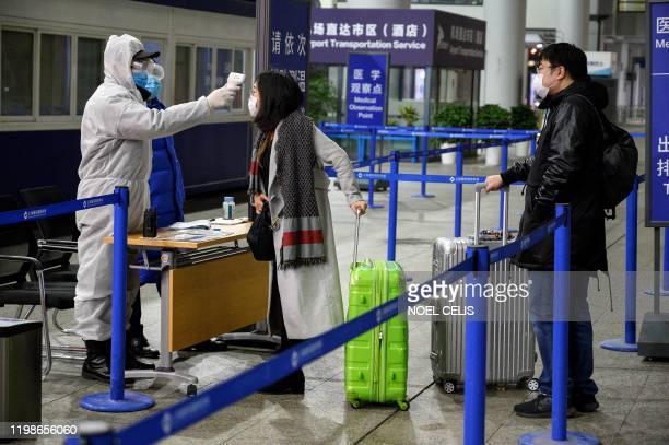 A security personnel checks the temperature of passengers arriving at the Shanghai Pudong International Airport in Shanghai on February 4 2020 The...