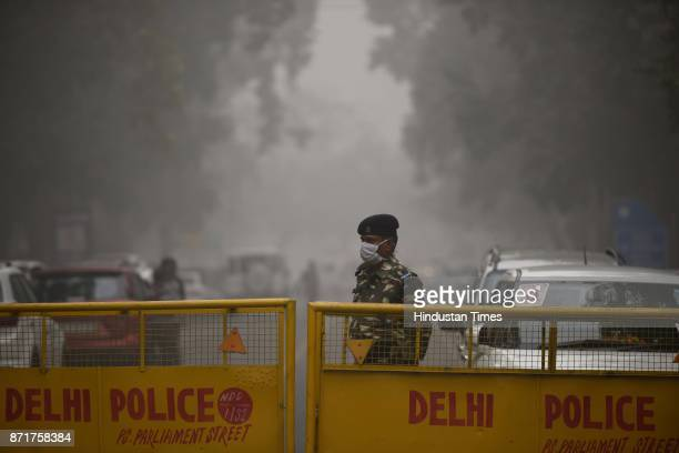 A security personnel covers his face to avoid pollution amid heavy smog on November 8 2017 in New Delhi India Delhi was enveloped in a thick blanket...