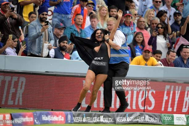 Security personnel detain a pitch invader during the 2019 Cricket World Cup final between England and New Zealand at Lord's Cricket Ground in London...