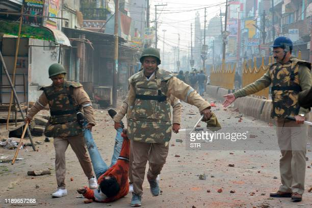 Security personnel detain a protester during demonstrations against India's new citizenship law in Meerut on December 20, 2019. - Five more...