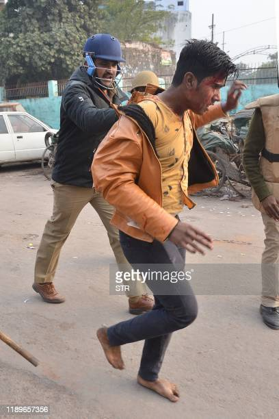 Security personnel detain a protester during demonstrations against India's new citizenship law in Kanpur on December 20, 2019. - Five more...