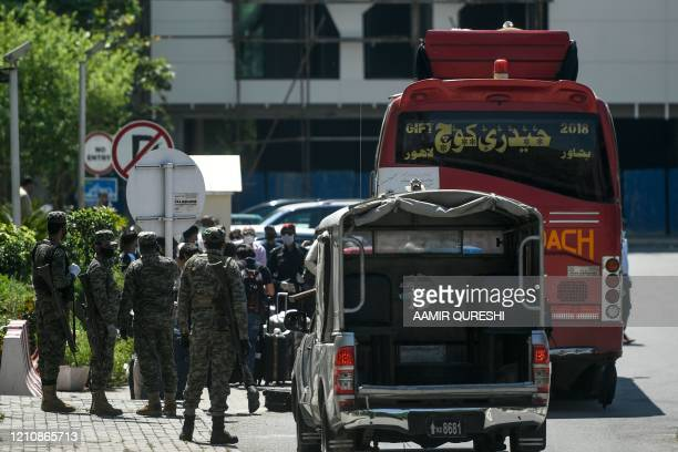 Security personnel escort a bus carrying international travelers who arrive at a hotel where they will be quarantined as a preventive measure against...