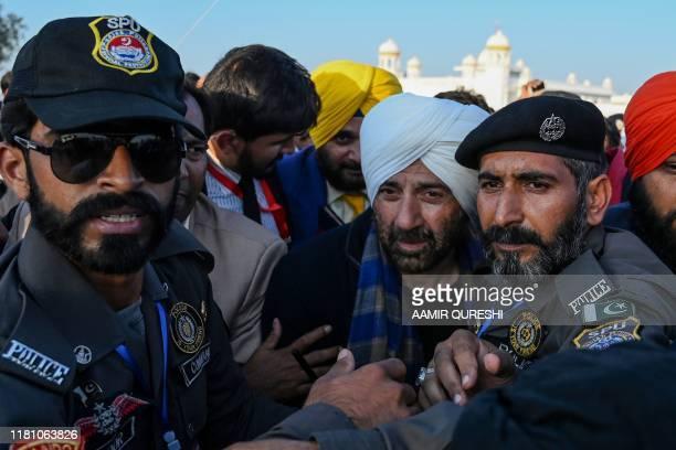 Security personnel escort Indian Bollywood actor Sunny Deol as he visits the Shrine of Baba Guru Nanak Dev at Gurdwara Darbar Sahib in Kartarpur near...