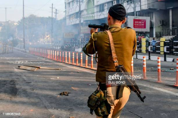 Security personnel fires tear gas during a curfew in Guwahati on December 12 following protests over the government's Citizenship Amendment Bill . -...