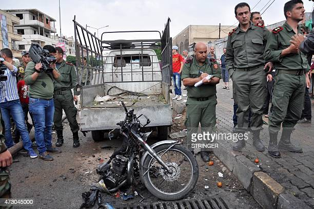 Security personnel gather around the remains of a motorcycle on May 12 after a double bomb blast in the Wadi Dahab neighbourhood of the central...