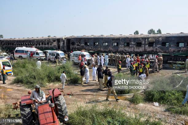 Security personnel gather infront of the burntout train carriages after a passenger train caught on fire near Rahim Yar Khan in Punjab province on...