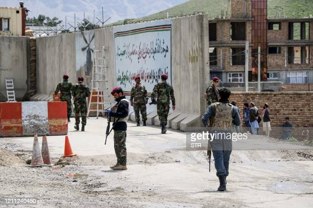Security personnel gather near a military outpost at the site where a suicide bomber attack occurred on the outskirts of Kabul on April 29 2020 A...