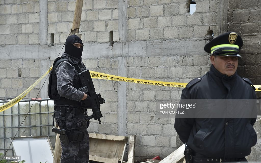 Security personnel guard the house at the end of the tunnel through which Mexican drug lord Joaquin 'El Chapo' Guzman could have escaped from the Altiplano prison, in Almoloya de Juarez, Mexico, on...