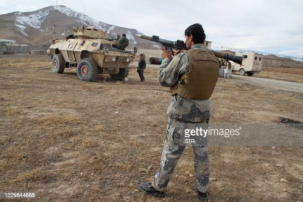 Security personnel holding a rocket-propelled grenade stands at a site after a suicide car bomber struck an army base on the outskirts of Ghazni...