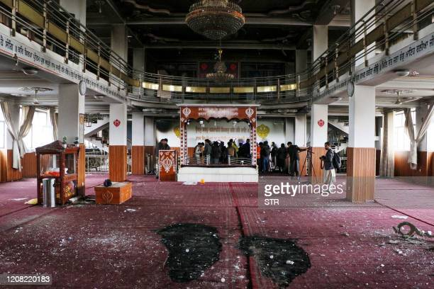 Security personnel inspect a damaged SikhHindu Temple alongside with media representatives following a gun attack in Kabul on March 25 2020 At least...