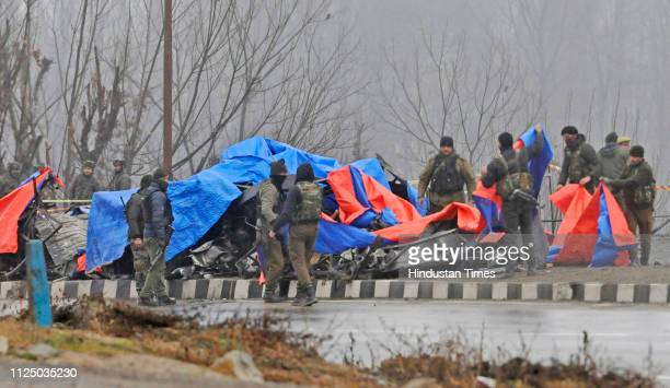 Security personnel inspect the blast site in Lethpora area of south Kashmir's Pulwama district some 25 kilometers south of Srinagar on February 15...