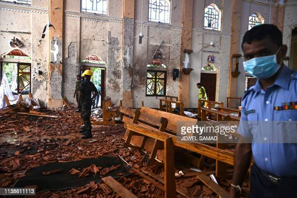 TOPSHOT Security personnel inspect the interior of St Sebastian's Church in Negombo on April 22 a day after the church was hit in series of bomb...