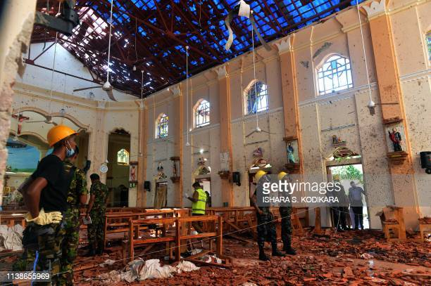 Security personnel inspect the interior of St. Sebastian's Church in Negombo on April 22 a day after the church was hit in series of bomb blasts...