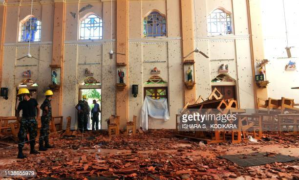 Security personnel inspect the interior of St Sebastian's Church in Negombo on April 22 a day after the church was hit in series of bomb blasts...