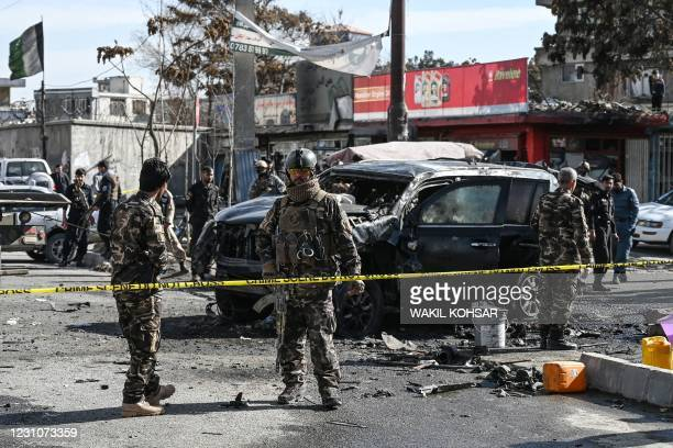Security personnel investigate a damaged armored car at the site after multiple bomb blasts, killing at least two people, in Kabul on February 10,...
