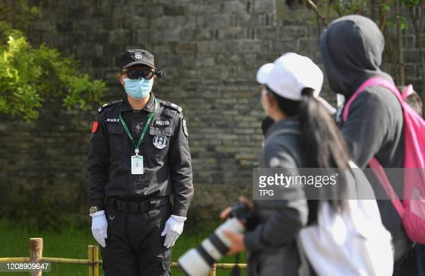 Security personnel is checking people's temperatures with a AR measuring glasses on 01th April, 2020 in Hangzhou,Zhejiang,China.