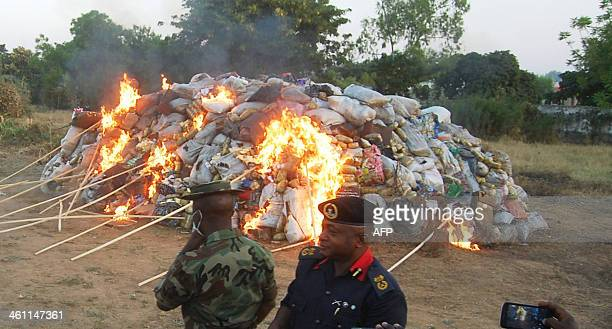 Security personnel keep watch as fire guts 10 metric tonnes of seized hard drugs destroyed by Nigeria's antinacortics agency NDLEA on December 6 2013...