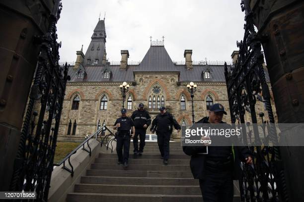 Security personnel leave the West Block building of Parliament Hill the temporary home to the House of Commons in Ottawa Ontario Canada on Friday...