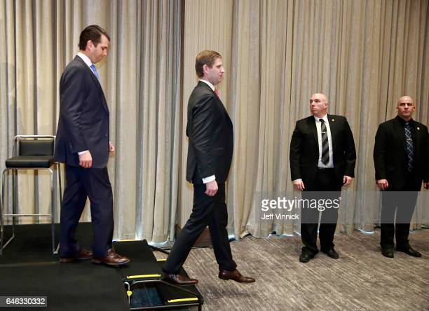 Security personnel look on as Donald Trump Jr and his brother Eric Trump leave the stage after a ceremony for the official opening of the Trump...
