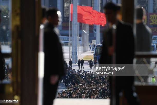 Security personnel look on as military delegates arrive at the Great Hall of the People before the closing session of the National People's Congress...