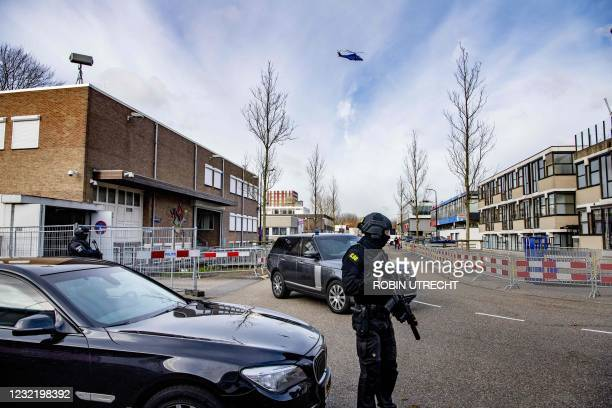 Security personnel members stand as a secure transport arrives at an extra secure court known as the Bunker, in Amsterdam, on April 9, 2021 prior to...