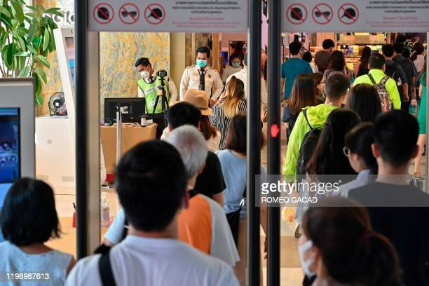 Security personnel operate a thermal temperature scanner on visitors at the entrance of a shopping in Bangkok on January 28 2020 Thailand has...