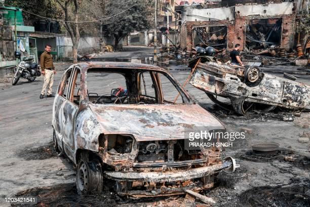 Security personnel patrols near burnt-out vehicles following clashes between people supporting and opposing a contentious amendment to India's...