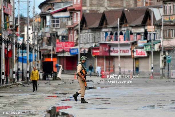 A security personnel patrols on a deserted road of the Lal Chowk area in Srinagar on August 19 2019 Some Kashmir schools reopened on August 19 but...