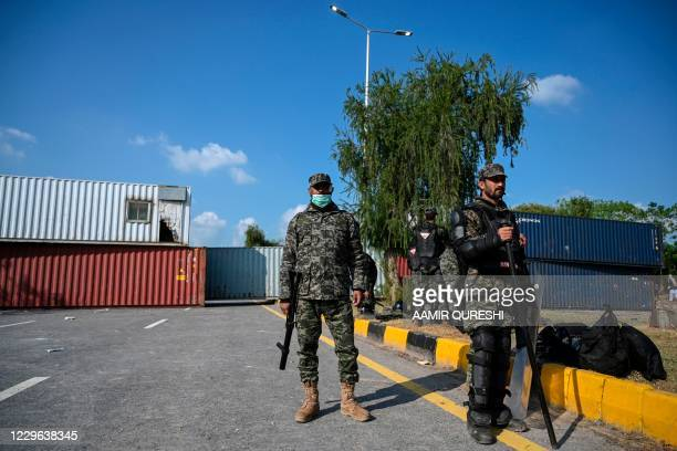 Security personnel prepare for their deployment beside shipping containers placed by authorities blocking the Islamabad-Rawalpindi highway to stop...