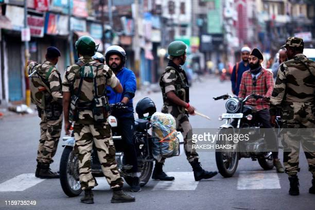TOPSHOT Security personnel question motorists on a street in Jammu on August 5 2019 Authorities in Indianadministered Kashmir placed large parts of...