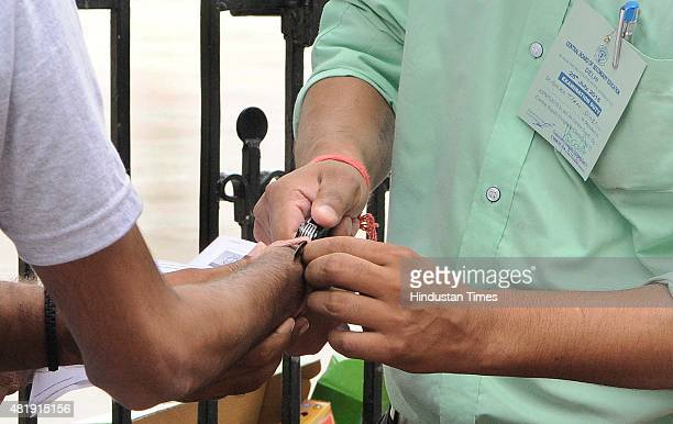 Security personnel removes a Mauli from an AIPMT aspirant's wrist as it was not allowed due to dress code at the entrance of an examination center at...